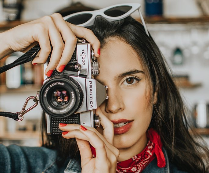 woman-holding-and-using-a-camera-3226441
