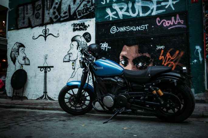 photo-of-motorcycle-parked-near-wall-with-graffiti-3269629